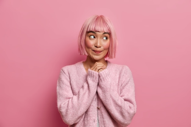 Innenaufnahme der verträumten hübschen jungen frau hat kurzes rosa haar, schaut mit glücklich zufriedenem ausdruck beiseite, hält hände zusammengedrückt, trägt pullover