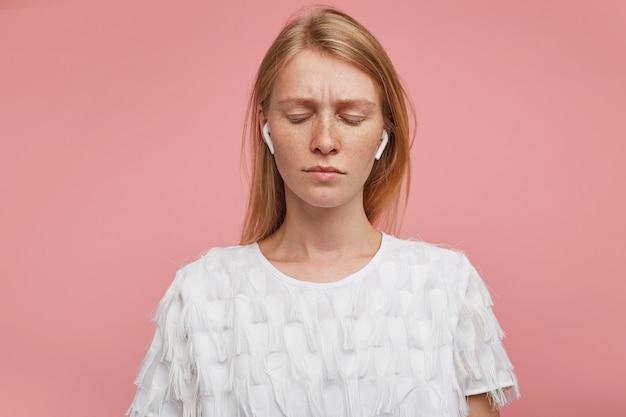 Innenaufnahme der verwirrten traurigen jungen rothaarigen frau, die die augenbrauen runzelt und die lippen mit geschlossenen augen gefaltet hält, gekleidet in weißes festliches t-shirt, während über rosa hintergrund posierend