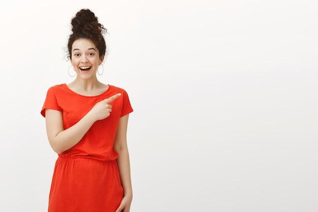 Innenaufnahme der zufriedenen glücklichen jungen frau mit dem lockigen haar im brötchen, das niedliches lässiges kleid trägt und auf die obere rechte ecke zeigt
