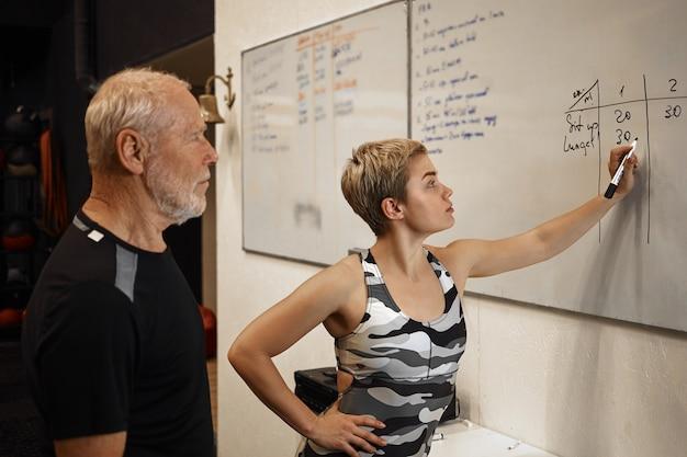 Innenaufnahme des älteren bärtigen mannes, der am fitnesscenter mit personal trainer der attraktiven frau aufwirft, der markierungsstift hält, um auf weiße tafel zu schreiben, crossfit-training zu planen. sport und bewegung