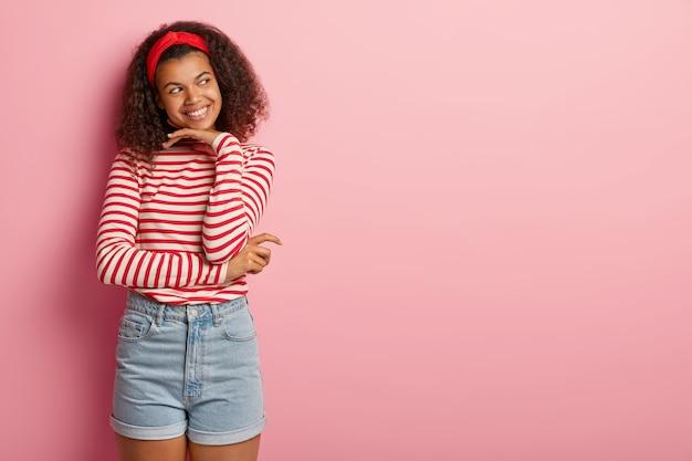 Innenaufnahme des angenehmen teenager-mädchens mit dem lockigen haar, das im gestreiften roten pullover aufwirft