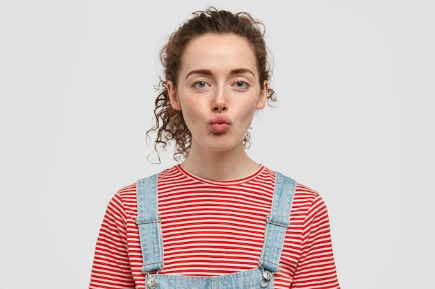 Innenaufnahme des attraktiven lockigen jungen weiblichen modells will jemanden auf distanz küssen, schmollt lippen