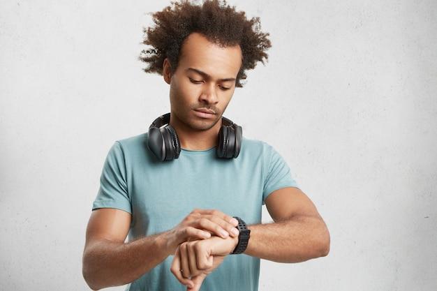 Innenaufnahme des attraktiven männlichen teenagers mit trendiger frisur, trägt lässiges t-shirt,