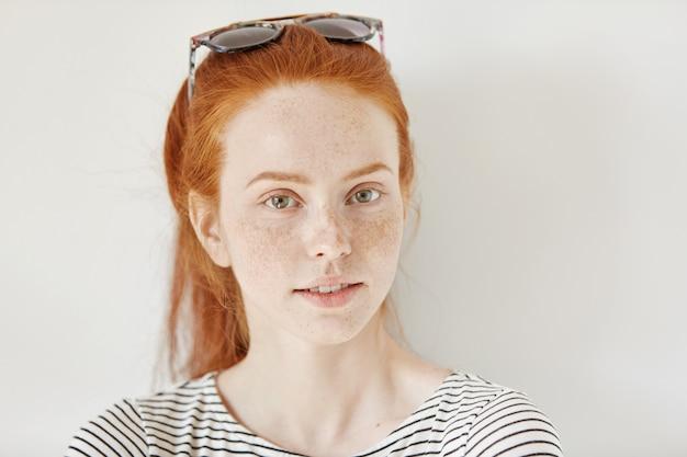 Innenaufnahme des attraktiven rothaarigen frauenmodells mit sommersprossen, die trendige sonnenbrille auf ihrem kopf und seemannsaufnahme tragen, die mit einem schwachen lächeln schauend