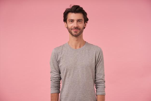 Innenaufnahme des bärtigen mannes mit trendigem haarschnitt stehend, mit leichtem lächeln schauend, grauen pullover tragend, positive haltung zeigend