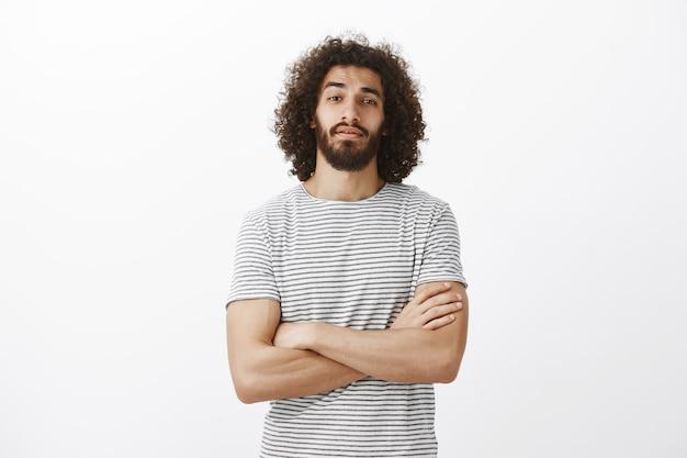 Innenaufnahme des beliebten gutaussehenden männlichen modells mit bart und afro-frisur, die hände auf der brust gekreuzt halten und mit erhobenem kinn schauen