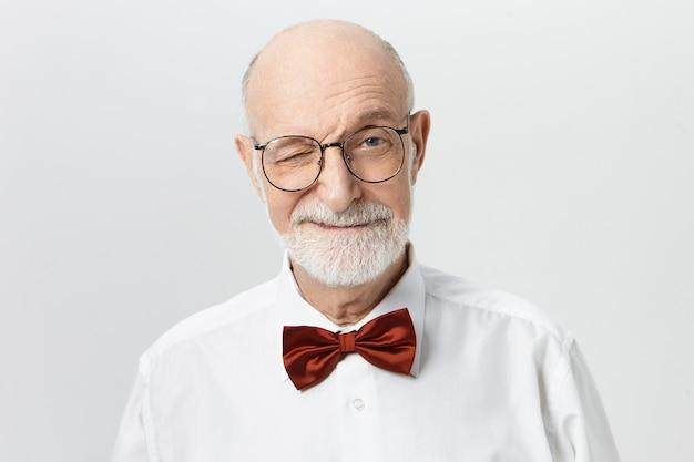 Innenaufnahme des charismatischen charmanten älteren europäischen mannes, der elegante rote fliege und brillen trägt, die spielerischen gesichtsausdruck haben, der mit lächeln zwinkert. körpersprache und menschliche emotionen