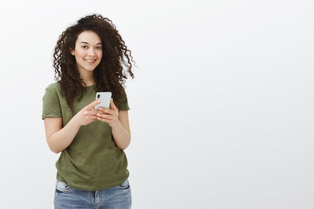 Innenaufnahme des charmanten flirty lockigen weiblichen angestellten im lässigen t-shirt