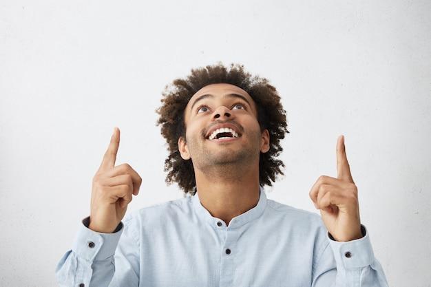 Innenaufnahme des eleganten glücklichen mannes mit afrikanischer frisur, die zeigefinger anhebt