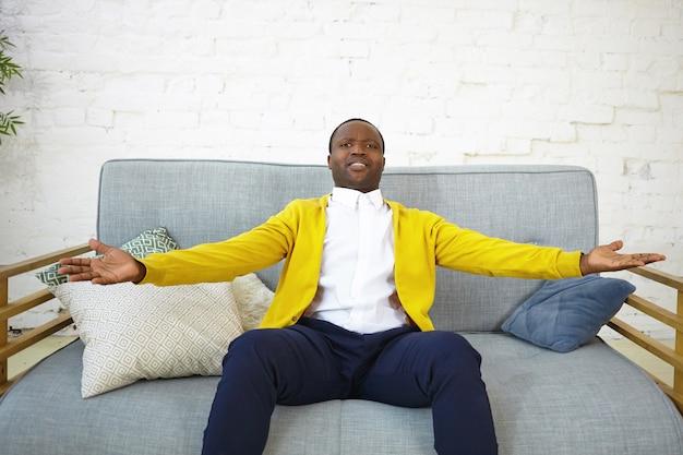 Innenaufnahme des emotionalen fröhlichen jungen afroamerikaners in der stilvollen kleidung, die auf bequemem grauem sofa im wohnzimmer sitzt, arme auseinander hält, aufgeregten gesichtsausdruck überglücklich