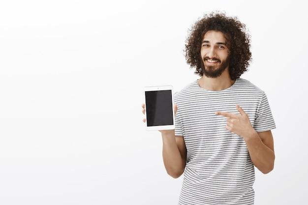 Innenaufnahme des erfreuten attraktiven männlichen sportlers mit bart- und afro-frisur, digitales tablett zeigend
