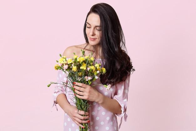 Innenaufnahme des erfreuten dunkelhaarigen weiblichen modells hält blumenstrauß, gekleidet in modischem kleid, lokalisiert auf rosa. romantische attraktive frau erhält blumen am 8. märz