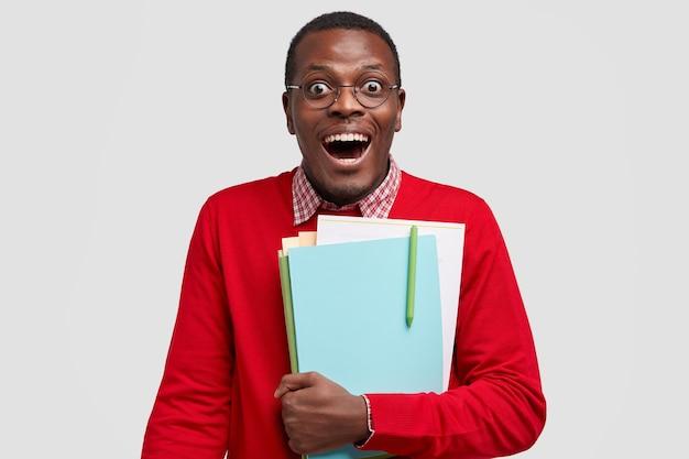 Innenaufnahme des erfreuten schwarzen mannes trägt roten pullover, trägt ordner, schaut glücklich direkt in die kamera