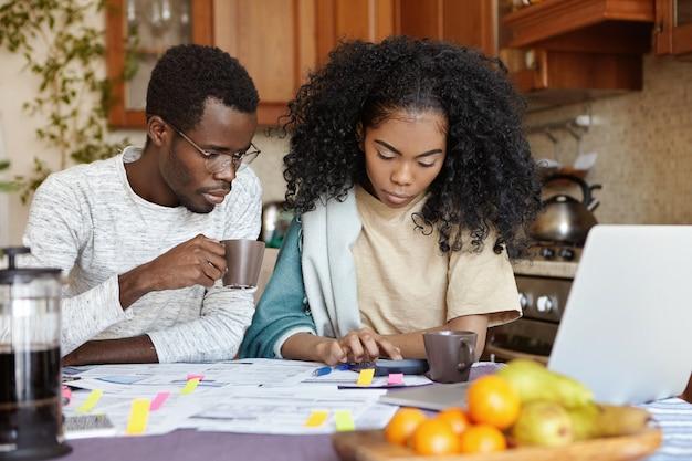 Innenaufnahme des ernsten afrikanischen mädchens unter verwendung des taschenrechners beim bezahlen von rechnungen, sitzend am küchentisch