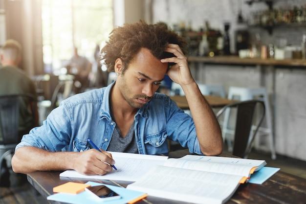 Innenaufnahme des fokussierten gutaussehenden stilvollen schwarzen europäischen universitätsstudenten, der ernsthaften konzentrierten gesichtsausdruck hat, während lektion am morgen im café lernt und mathematische probleme löst