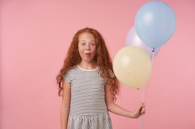 Innenaufnahme des freudigen langhaarigen lockigen weiblichen kindes mit foxy haar, das spaß über rosa hintergrund macht, lässiges gestreiftes kleid trägt, kamera glücklich betrachtet und zunge zeigt
