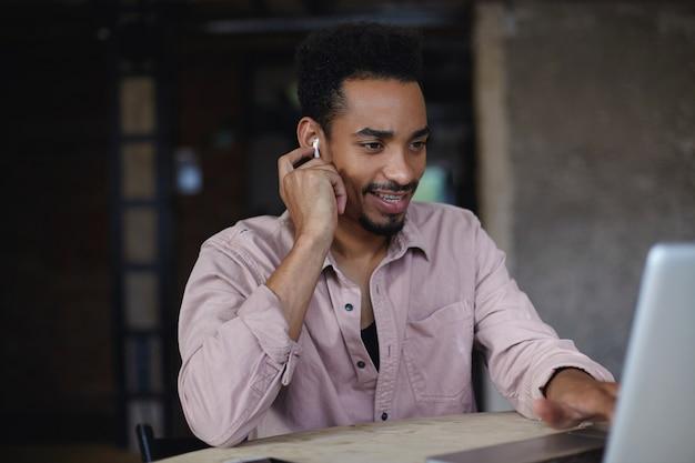 Innenaufnahme des fröhlichen jungen dunkelhäutigen bärtigen mannes im beige hemd, der über dem modernen büroinnenraum sitzt und videoanruf mit laptop hat, leicht lächelt und hand auf ohrhörer in seinem ohr hält