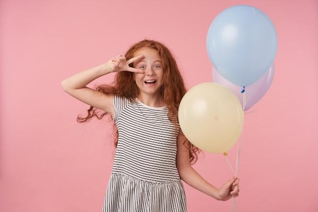 Innenaufnahme des fröhlichen lockigen mädchens mit dem gelockten langen haar, das gestreiftes kleid über rosa hintergrund trägt, farbige luftballons in der hand hält und breit zur kamera lächelt, die friedensgeste zu ihrem gesicht erhöht
