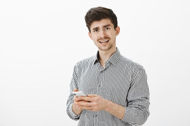 Innenaufnahme des frustrierten unzufriedenen reifen mannes mit schnurrbart im lässigen gestreiften hemd, der befragt schaut, während er frage stellt und smartphone hält, verwirrende nachricht empfängt