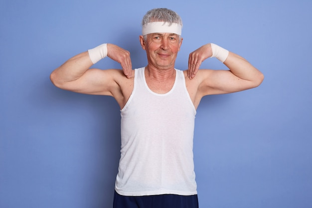Innenaufnahme des glücklichen energetischen älteren mannes, der körperliches training gegen blaue wand genießt, körperliche übung tut, finger auf seinen schultern hält