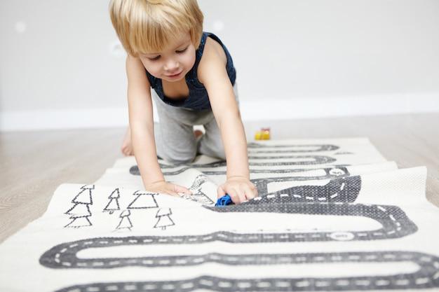 Innenaufnahme des glücklichen fröhlichen kaukasischen zweijährigen jungen mit blonden haaren, die mit seinen spielzeugen spielen, auf teppich im kinderzimmer kriechend, interessiert aussehend.