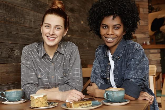 Innenaufnahme des glücklichen fröhlichen samesex interracial weiblichen paares, das kaffee trinkt