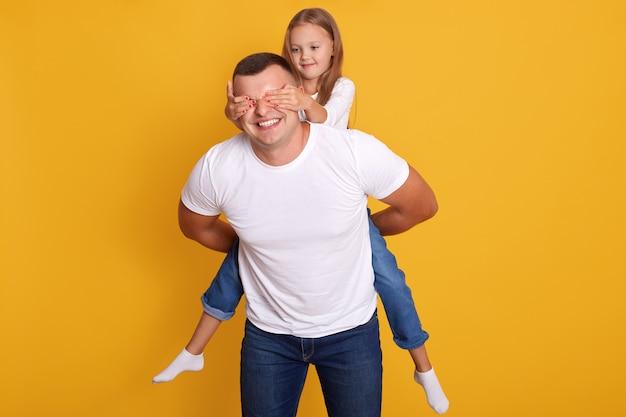 Innenaufnahme des glücklichen vaters huckepack tochter, während charmantes kind seine augen schließt, glücklicher mann mit entzückendem mädchen