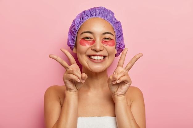 Innenaufnahme des gut aussehenden lächelnden asiatischen mädchens machen friedensgeste mit beiden händen, genießt uder augenbehandlung, trägt kollagenpflaster auf, besucht kosmetikerin trägt duschhaube auf kopf. gesichtspflegekonzept