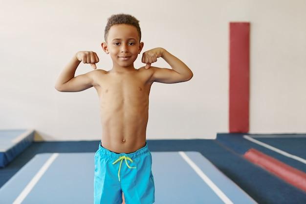 Innenaufnahme des hübschen afroamerikanischen jungen mit athletischem körper und starkem waffentraining am fitnesscenter