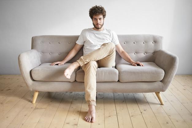 Innenaufnahme des hübschen jungen bärtigen mannes, der weißes t-shirt und blaue jeans trägt, die barfuß auf bequemer grauer couch sitzen, und lächelnde, leere copyspace-wand