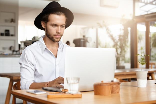 Innenaufnahme des hübschen jungen freiberuflers im schwarzen hut, der am holztisch vor dem allgemeinen laptop sitzt und bildschirm mit ernstem und konzentriertem ausdruck betrachtet, unter verwendung des notizbuchs für fernarbeit