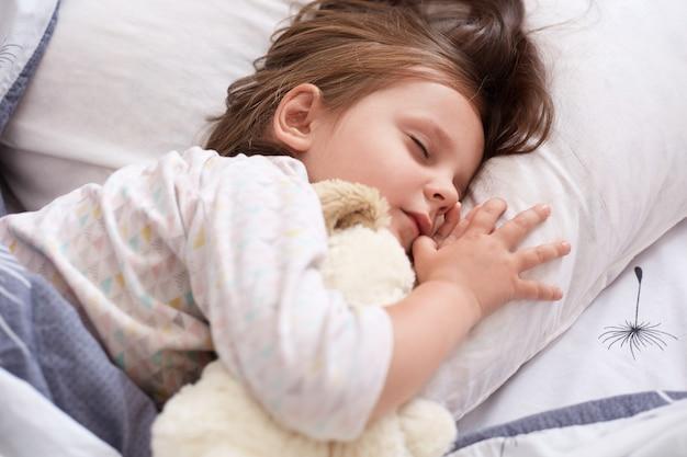 Innenaufnahme des hübschen kleinen mädchens, das weißes weiches hundespielzeug beim schlafen im bett zu hause umarmt