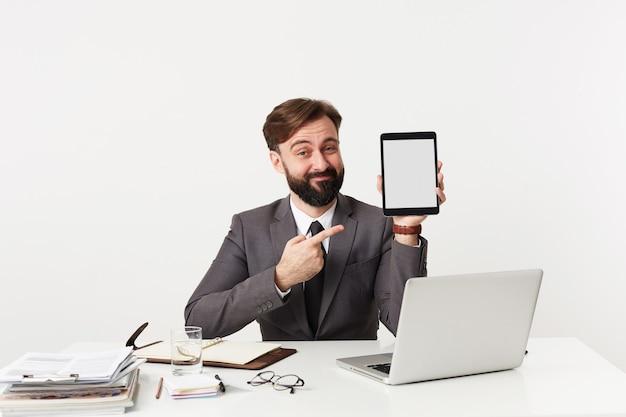 Innenaufnahme des jungen brünetten mannes in der formellen kleidung, die am arbeitstisch sitzt und mit ironischem gesicht nach vorne schaut, tablet-pc hält und mit erhobener hand darauf zeigt