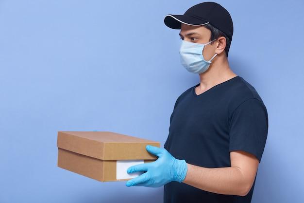 Innenaufnahme des jungen lieferboten mit karton in den händen, mann, der t-shirt, kappe und schutzmaske und latexhandschuhe trägt