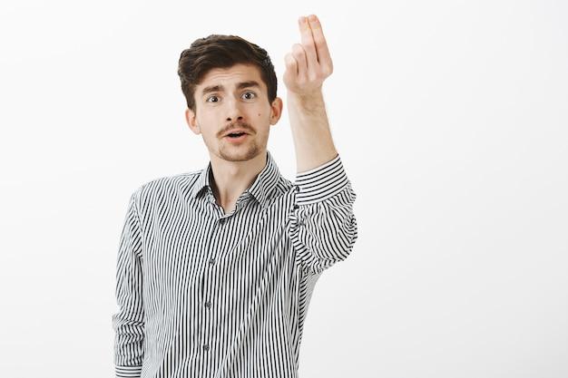 Innenaufnahme des lustigen gewöhnlichen europäischen mannes mit schnurrbart und bart, der leidenschaftlich spricht, während er hand mit italienischer geste hebt