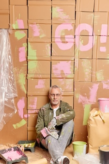Innenaufnahme des malers des reifen mannes sitzt auf dem boden und ruht sich aus, nachdem er seine hausfarben verwandelt hat.