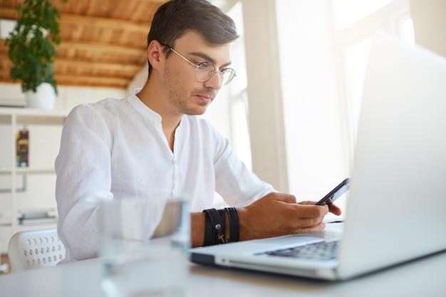 Innenaufnahme des nachdenklichen hübschen jungen geschäftsmannes trägt weißes hemd im büro