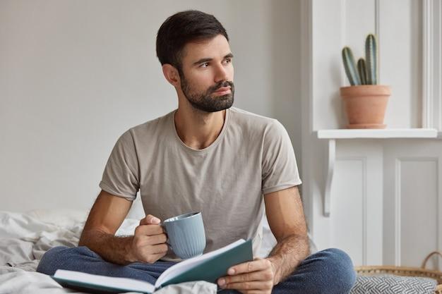 Innenaufnahme des nachdenklichen jungen kaukasischen kerls mit dickem bart, der tief in gedanken ist, buch und tasse tee hält, posiert auf bett