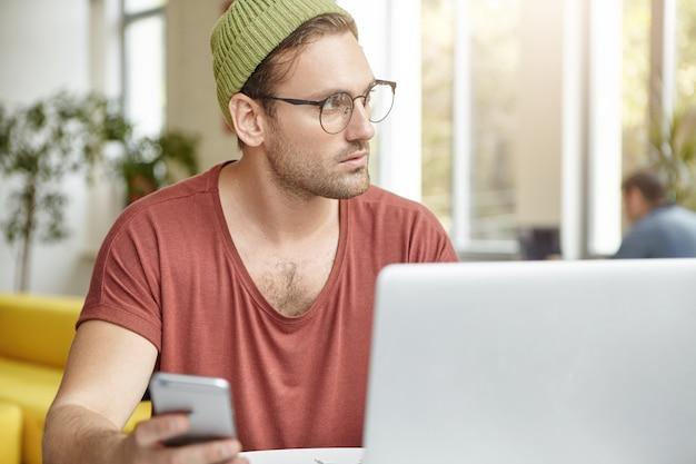 Innenaufnahme des nachdenklichen männlichen schriftstellers arbeitet am schreiben eines neuen buches oder kapitels, hält smartphone in der hand