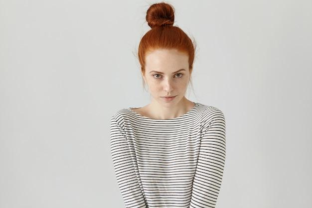 Innenaufnahme des niedlichen rothaarigen mädchens mit dem haarknoten, der lässiges gestreiftes langärmeliges t-shirt trägt, ihre haltung, die schüchternheit ausdrückt. schöne junge frau, die an der leeren wand aufwirft