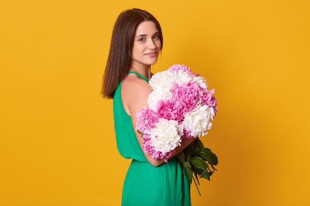 Innenaufnahme des porträts der charmanten stilvollen frau im eleganten grünen sommerkleid lokalisiert über gelb