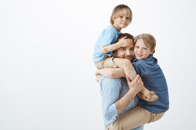 Innenaufnahme des positiven glücklichen familienmenschen, der sohn mit vitiligo auf den schultern und niedlichem kind auf der brust hält, breit lächelt und sich beim spielen mit liebenden kindern freudig fühlt