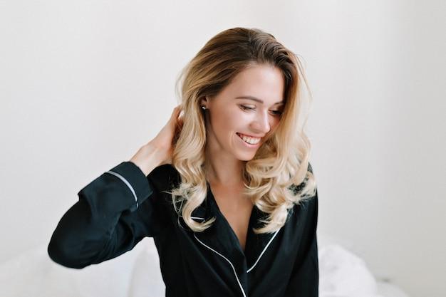 Innenaufnahme des reizenden jungen weiblichen modells mit blonden haaren gekleideter nachtwäsche, die im bett mit wunderbarem lächeln sitzt