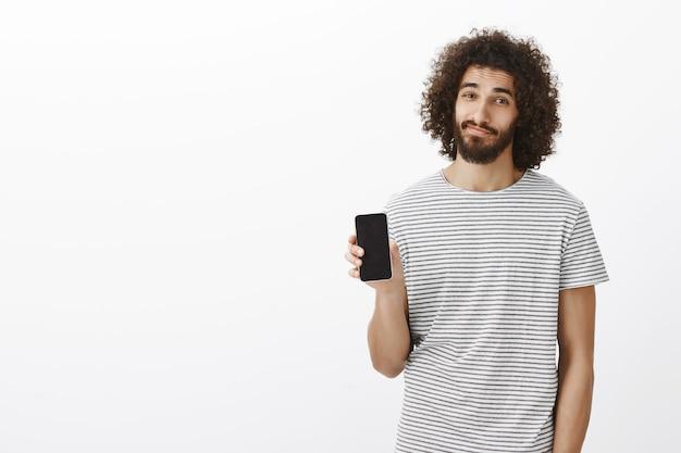Innenaufnahme des ruhigen lässigen attraktiven männlichen mitarbeiters im gestreiften t-shirt, das schwarzes smartphone zeigt und mit entspanntem erfreutem ausdruck lächelt