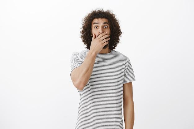 Innenaufnahme des schockierten hübschen östlichen freundes im gestreiften t-shirt, mund mit handfläche bedeckend