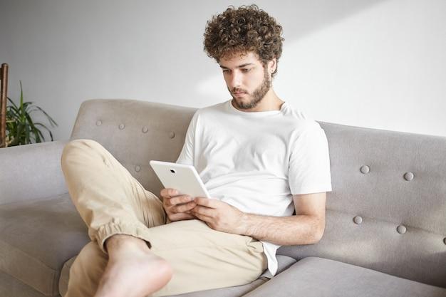 Innenaufnahme des stilvollen jungen kaukasischen geschäftsmannes in der freizeitkleidung, die geschäftsnachrichten liest oder e-mail auf touchpad prüft, auf sofa vor der arbeit sitzend. konzept für menschen, beruf, technologie und beruf