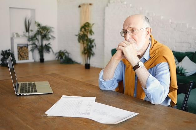 Innenaufnahme des unglücklichen traurigen älteren bärtigen männlichen unternehmers, der am schreibtisch mit laptop und papieren sitzt, deprimierten gesichtsausdruck, frustriert von finanziellen problemen, hände unter seinem kinn haltend