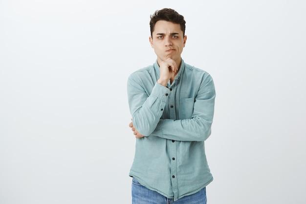 Innenaufnahme des unzufriedenen unbeeindruckten hübschen jungen männlichen studenten im trendigen hemd