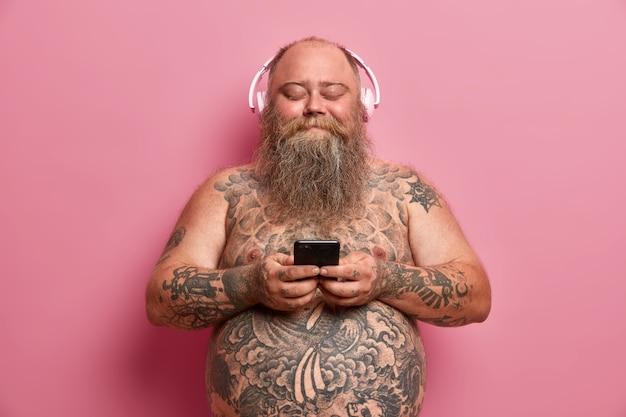 Innenaufnahme des zufriedenen erwachsenen fatso-mannes hält handy, verwendet musik-app, trägt stereo-kopfhörer an den ohren, hört lied, steht nackt, hat körper tätowiert, isoliert auf rosa wand. übergewicht