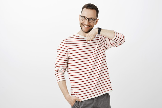 Innenaufnahme des zufriedenen glücklichen europäischen mannes mit der borste in der brille, die hand hebend und hörend, ton zu hören, mit der qualität des gadgets zufrieden zu sein